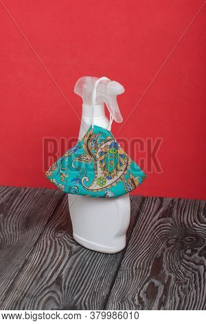 White Plastic Bottle With Spray. Cleaning Spray. Next To The Face Mask To Protect Against The Virus.
