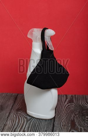 White Plastic Bottle With Spray. Cleaning Spray. Next To It Is A Black Face Mask To Protect Against