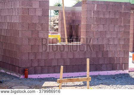 Building Site Of A House Under Construction. Unfinished House Wall Made From Concrete Blocks