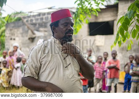 An African Older Man, The Mayor Of His Village In Red Muslim Taqiyyah Hat And White Dress. Small Rem