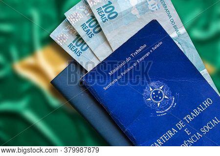 Brazilian Work Card With Brazilian Money Isolated On Brazilian Flag Defocused Background. Written In