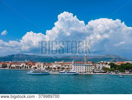 Panoramic Image Of Split City Harbor. Sea, Passenger Ships, Historic Houses, Tower With Mountains