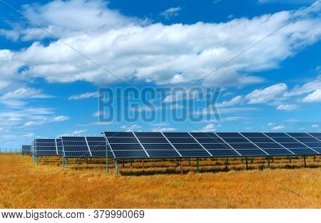 Solar Power Plant, Blue Solar Panels On Autumn Orange Grass Field Under Blue Sky With Clouds