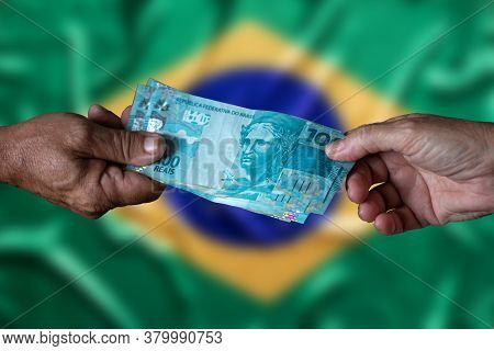 Brazilian Money Bills. One Hundred Reais. Man's Hand And Woman's Hand Holding One Hundred Reais Note