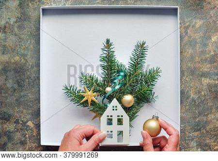 Christmas Decorations, Flat Lay With Hands Making Decorated Box With House, Fir Twigs And Golden Tri