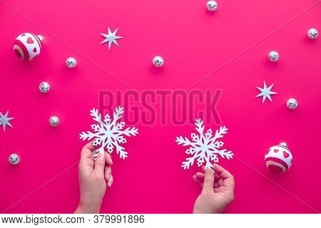 Christmas Background With White Trinkets, Toys, Xmas Decorations On Vibrant Bright Pink Paper. Hands