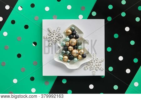 Xmas Baubles In Fir Shaped Plate White Square On Layered Green And Black Paper, Geometric Paper Shap