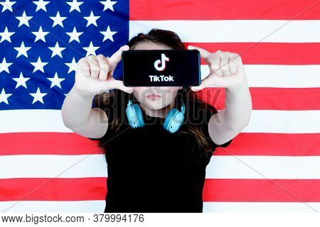 A Teenager Holds A Smartphone With The Tiktok Logo And Against The Background Of The American Flag.
