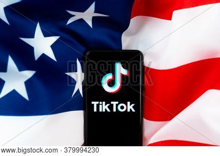 Tiktok Application Logo On A Smartphone With American Flag Background. Donald Trump To Ban Tiktok In