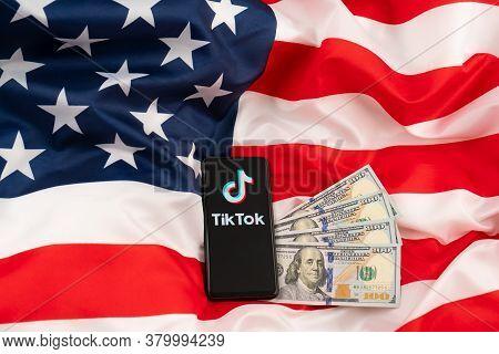 Tiktok Logo On A Smartphone And Us Dollars. Concept For Tik Tok Ban By Donald Trump. Russia, Kazan -