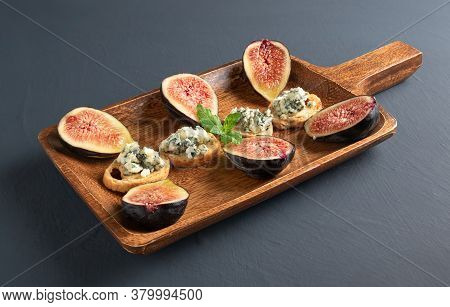 Toasts With Roquefort Cheese And Fresh Figs, On A Wooden Serving Board