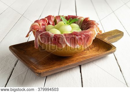 Melon With Air Dried Ham, Served In Halved Melon Stuffed With Serrano Ham And Melon Balls. On White