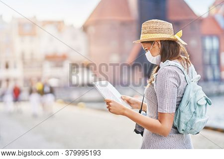 Female tourist wearing a mask sightseeing Gdansk Poland in summer
