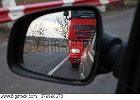 Truck In The Mirror Of Passenger Car. Truck Chasing Car.