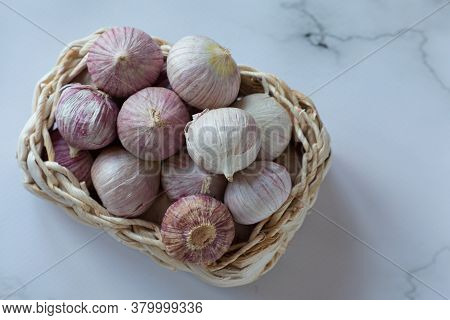 Fresh Solo Garlic Bulbs In A Basket On A White Background. They Are Used For Cooking And Grown In As