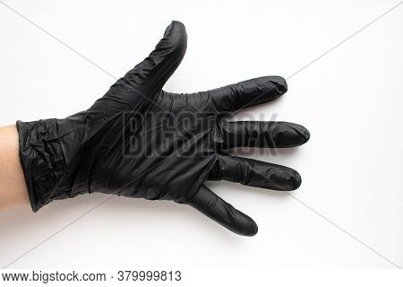 Hand In A Black Surgical Medical Glove, Isolated On A White Background. Production Of Rubber Protect