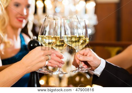 Good friends - man and women, drinking wine and clinking glasses in a fine dining restaurant, each with a glass in hand, a large chandelier is in Background