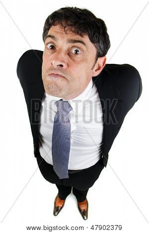 Humorous high angle full length portrait of a businessman with a bad attitude glaring up at the camera with a belligerent expression and his arms behind his back poster