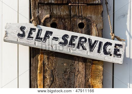 hand written self-service sign on a weathered oaken pole poster