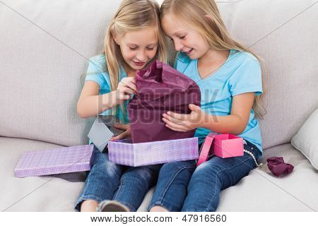 Young twins unwrapping birthday gift sitting on a couch in the living room