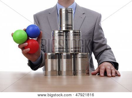 Businessman holding balls for tin can alley style business challenge concept for competition, chance, fortune or opportunity