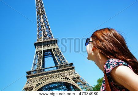 Young attractive happy woman looking at Eiffel Tower in Paris, France