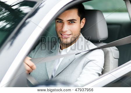 Handsome man fastening seat belt