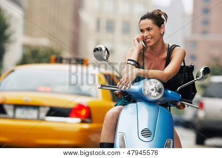 Young happy woman using mobile phone on moped poster