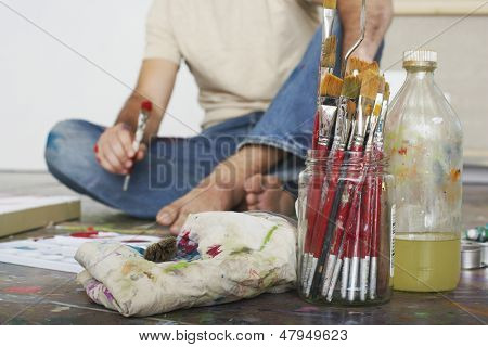 Low section of a male artist sitting on floor with paint brushes and materials