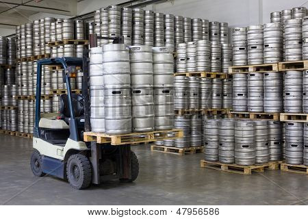 Forklift loading beer kegs in warehouse brewery  poster