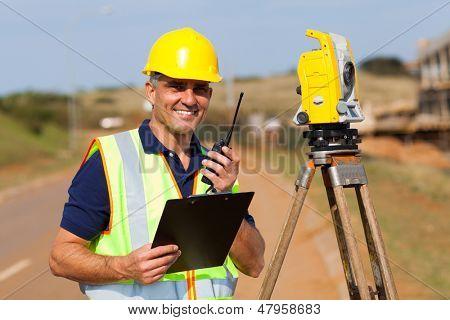 senior land surveyor working at road construction site poster