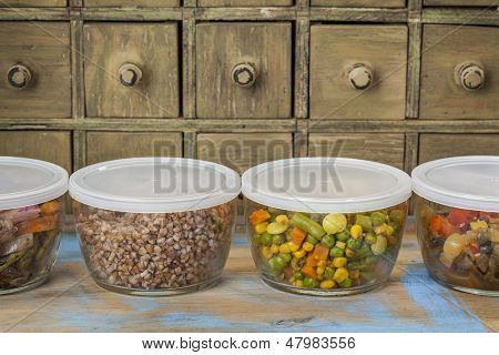 dinner leftovers (buckwheat kasha, vegetables, stir fry)  in glass  containers with drawer cabinet in background