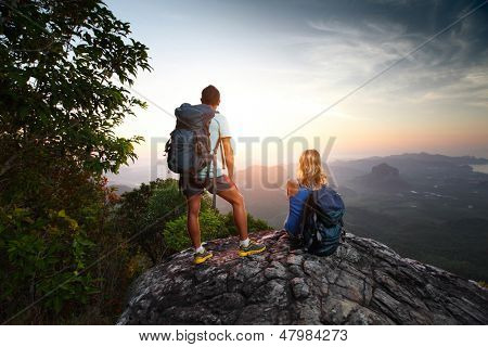 Two hikers enjoying sunrise from top of a mountain
