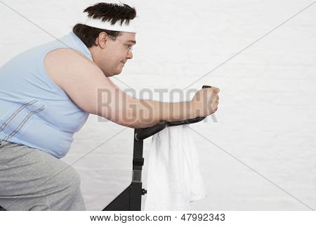 Side view of an overweight man on exercise bike against white background