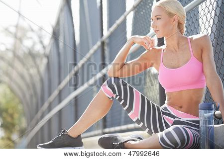 Fit Athlete Sits Along A Pathway