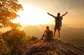 Two hikers enjoying sunrise from top of a mountain poster