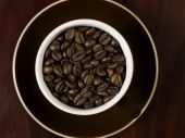 High angle view of coffee beans in a cup with a wooden background. poster