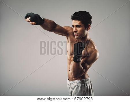 Fit Young Guy Shadowboxing On Grey Background