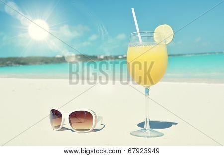 Orange juice and sunglasses on the beach. Exuma, Bahamas poster