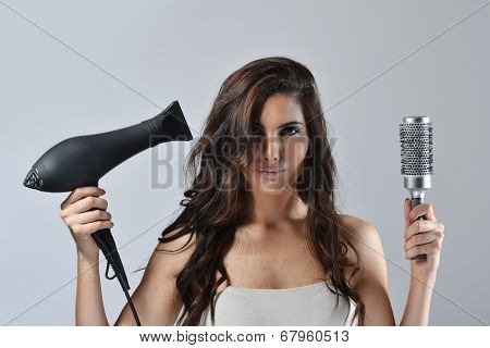 Beautiful young woman with the hair dryer and brush