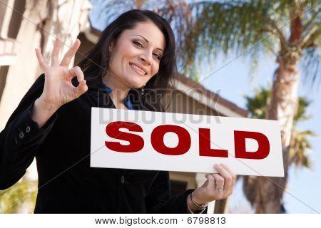 Atraente mulher hispânica segurando vendeu a placa na frente de casa