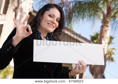Happy Attractive Hispanic Woman Holding Blank Sign in Front of House. poster