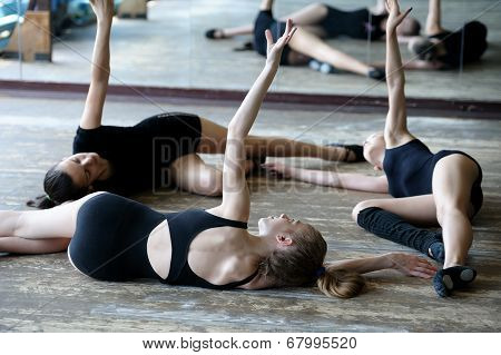 Three ballet dancers on the floor during rehearsal