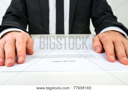 Businessman Reading A Document With Focus To The Text Terms And Conditions