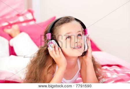 Adorable Little Girl Listening Music Lying On Her Bed