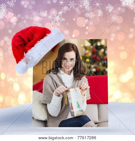 Brunette opening a gift on the couch at christmas against pink abstract light spot design