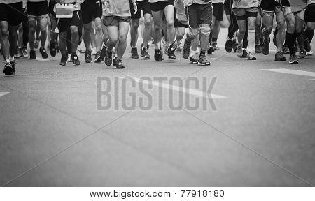 Unidentified marathon athletes legs running on city road poster