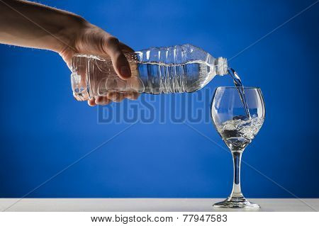 Hand pouring pure fresh water from a plastic bottle into a crystal clean stemmed glass on a white table close-up on blue background poster