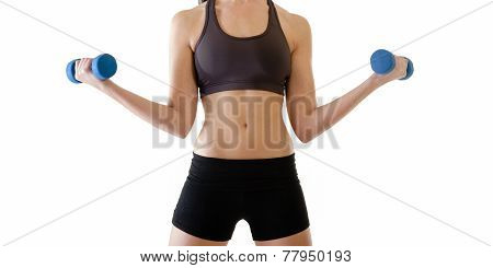 Young attractive girl exercising with pair of dumbbells
