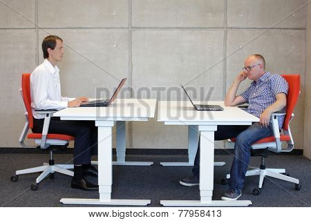 man working in correct sitting posture in office watching his colleague sitting in bad position at workstation